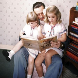 Walt Disney reading to a young Diane Disney and her sister.