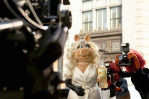 "Miss Piggy―diva, fashion icon and star of Disney's ""Muppets Most Wanted""―is photographed by the paparazzi (aka Animal) during the filming of Lipton's ""Be More Tea"" commercial."