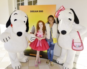 Francesca Capaldi and Skai Jackson posed with Snoopy and Belle in front of poster for the new Peanuts Movie